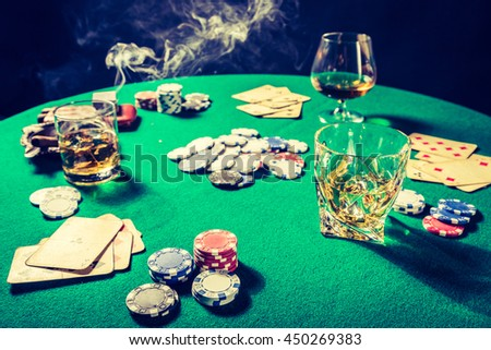 Closeup of gambling table with whiskey, cigar and cards - stock photo