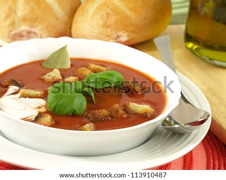 Closeup of garnished tomato soup with croutons and rolls in a background - stock photo