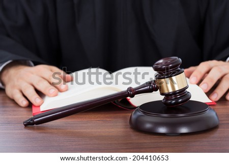 Closeup of gavel placed on block with judge reading law book at desk - stock photo