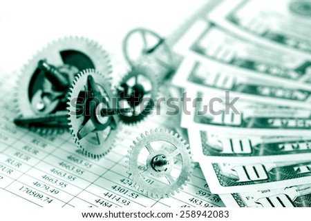Closeup of gears and dollar bank notes on paper list with digits - stock photo