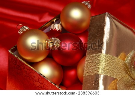 closeup of gift box with golden christmas balls over red silk background. festive decoration - stock photo