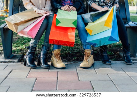 Closeup of girls with colorful shopping bags - stock photo