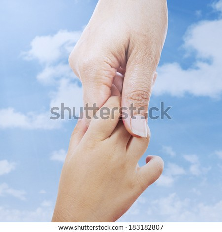 Closeup of giving a helping hand to another - stock photo
