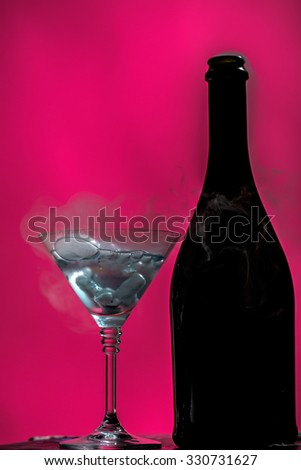 Closeup of glamour open full champagne wive sweet or dry drink green glass bottle and goblet with white smoke and ice for celebration christmas or new year on pink background, vertical picture - stock photo