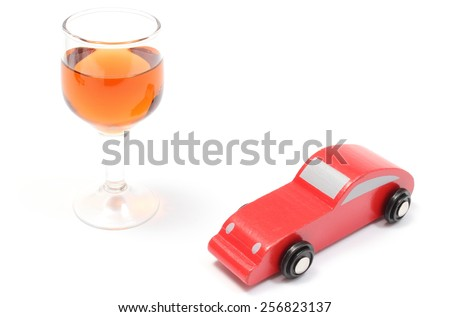 Closeup of glass of wine with old wooden toy car, car and alcohol, don't drink and drive concept. Isolated on white background - stock photo