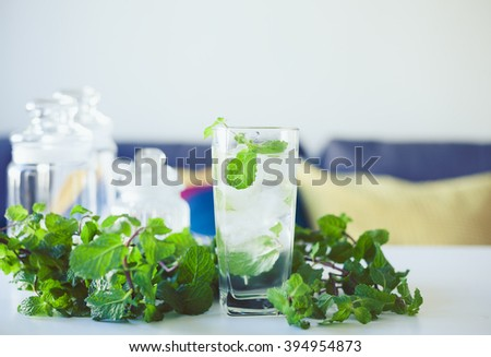 Closeup of glass with lemonade and mint leaves around. Refreshment in summer day. - stock photo