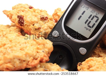 Closeup of glucometer and oatmeal cookies, concept for diabetes and healthy nutrition - stock photo