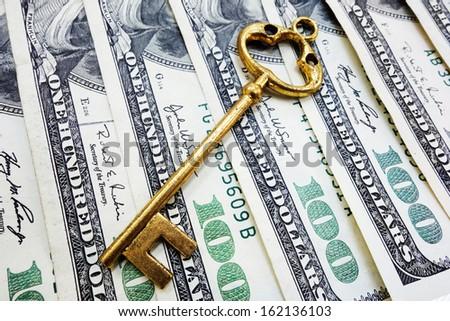 Closeup of gold key on hundred dollar bills                                - stock photo