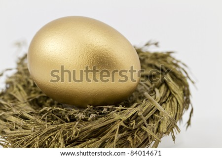 Closeup of gold nest egg set in sparkling gold nest; selective focus on nest egg; - stock photo
