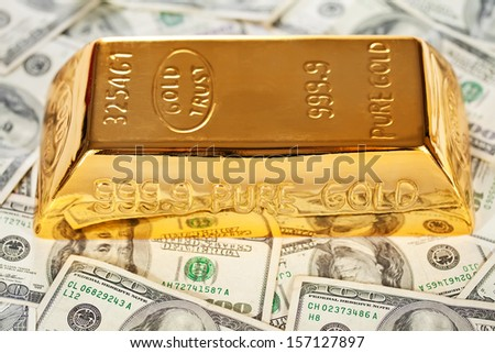 Closeup of golden  bullion on hundred dollars banknotes background - stock photo