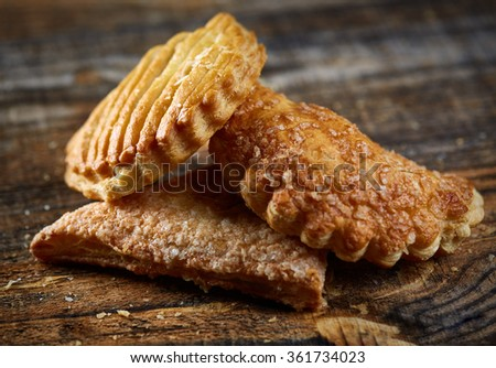 Closeup of golden crispy pastry on wooden board - stock photo