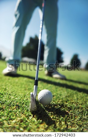 Closeup of golfer with iron hitting tee shot - stock photo