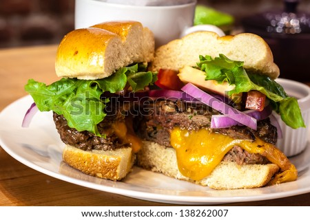 Closeup of gourmet hamburger with melted cheese and toppings on bun with side of sweet potato french fries - stock photo