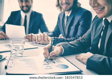 Closeup of graphs and chart analyzed by smiling business people - stock photo