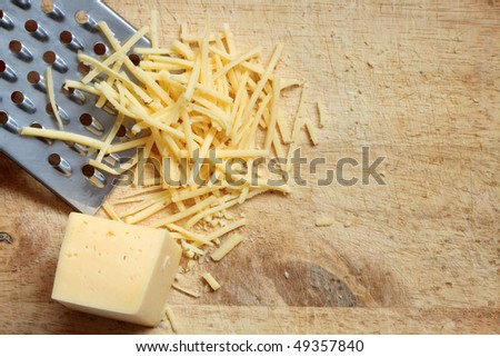Closeup of grated cheese and grater lying on wooden cutting board - stock photo