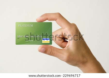 closeup of green credit card holded by hand. - stock photo