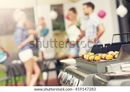 Closeup of grilled shashliks and hamburgers on grate - stock photo