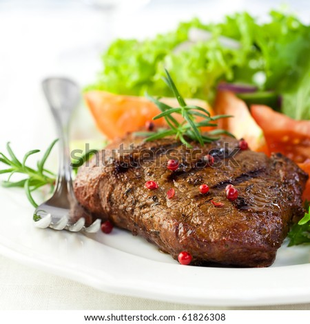 Closeup of grilled steak with pepercorns and rosemary - stock photo