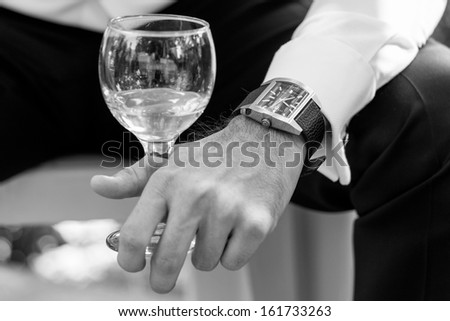 Closeup of groom and business man with glass of wine and watch - stock photo