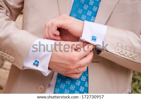 closeup of groom's arms fixing his blue cuff-links - stock photo