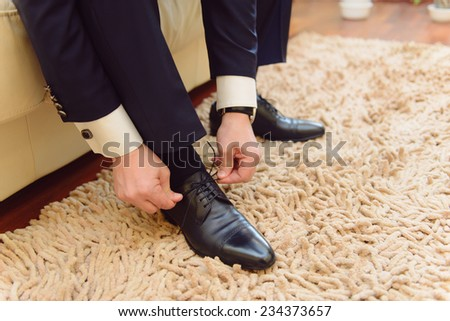 closeup of groom's hand tying bow on shoes at home - stock photo
