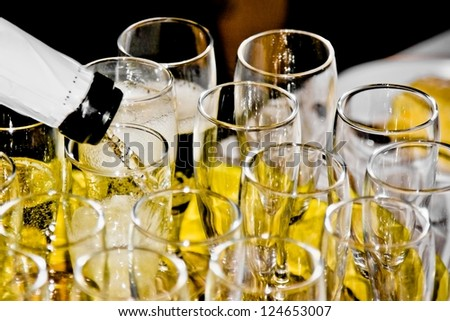 closeup of group of flutes of champagne on festive table and one is being filled - stock photo
