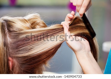 Closeup of hair dresser combing client's hair in salon - stock photo