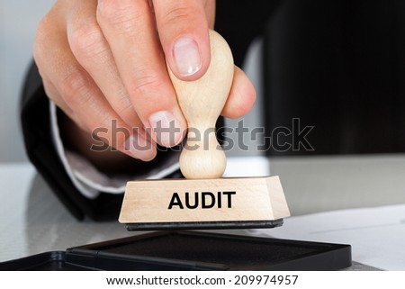 Closeup of hand holding rubber stamp with Audit sign at table in office - stock photo