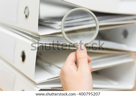 closeup of hand using of magnifying glass to inspect stack of documentation - stock photo