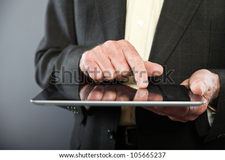 Closeup of hand using tablet from senior man in dark suit against grey wall. Well dressed. Studio shot. - stock photo