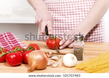 closeup of hands cutting tomatoes for spaghetti - stock photo