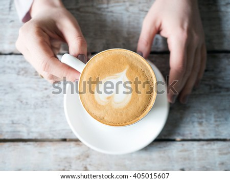 Closeup of hands holding warm Cappuccino with Froth and Heart Shape   - stock photo