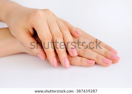 Closeup of hands of a young woman with pink manicure on nails against white background - stock photo