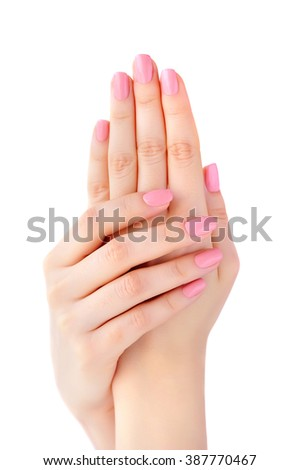 Closeup of hands of a young woman with pink manicure on nails isolated on white background - stock photo