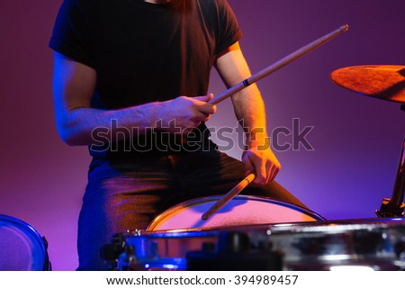Closeup of hands of man drummer sitting and playing drums with drumsticks over dark background - stock photo