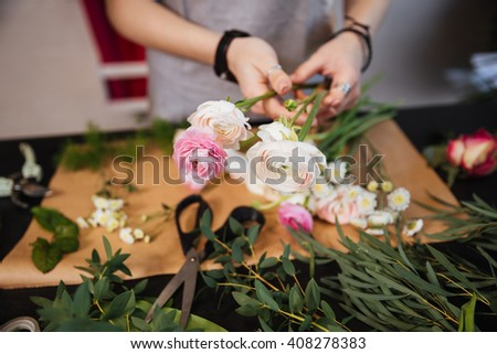 Closeup of hands of young woman florist creating bouquet of pink roses on the table - stock photo