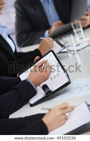 Closeup of hands on business meeting at office writing notes to personal organizer, - stock photo