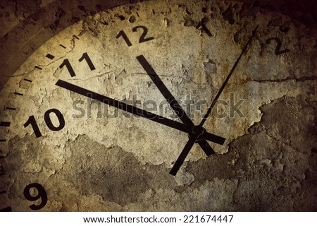 Closeup of hands on grunge clock face - stock photo