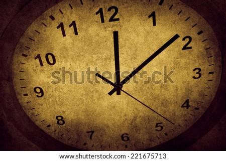 Closeup of hands on grunge clock face - stock photo