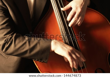 Closeup of hands plucking fingerboard of double bass - stock photo