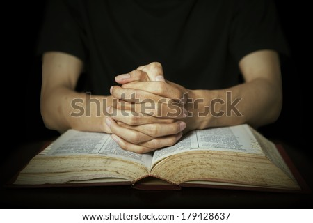 Closeup of hands praying on bible - stock photo