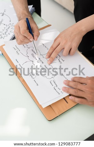 Closeup of hands working with financial plan - stock photo