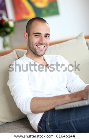 Closeup of handsome man websurfing on laptop computer - stock photo