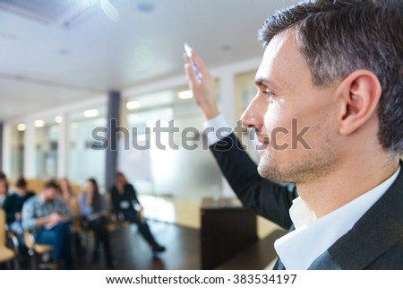 Closeup of handsome serious speaker standing with raised hand on business meeting in conference hall - stock photo
