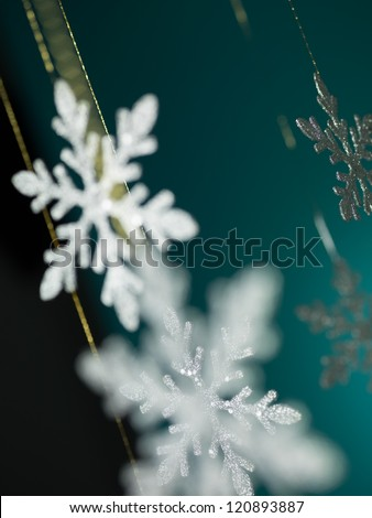 closeup of hanging christmas decorations in shape of snowflakes on blue background - stock photo