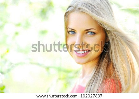 Closeup of happy cheerful smiling young beautiful blond woman, outdoors - stock photo