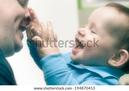 Closeup of happy child boy playing with his daddy. - stock photo