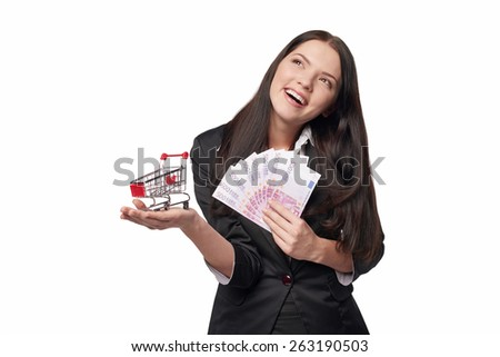 Closeup of happy excited young woman with euro cash money in one hand and small empty shopping cart in other hand, looking to the side at blank copy space, isolated on white background - stock photo