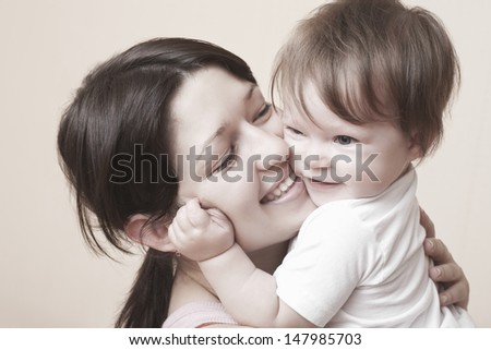 Closeup of happy mother hugging baby girl over colored background - stock photo