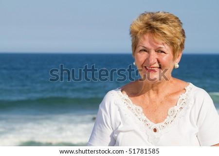 closeup of happy senior woman on beach - stock photo